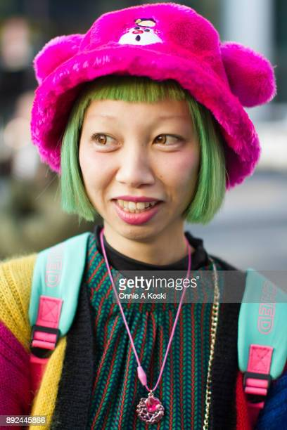 Otomo wearing a bright pink hat an Ochin sweater green hair brown contact lenses red and green leaf pattern dress a rainbow striped shoulder bag with...