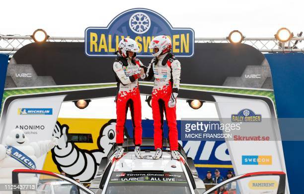 Ott Tanak and his codriver Martin Jarveoja from Estonia stand on their Toyota Yaris WRC car as they celebrate after winning the FIA World Rally...