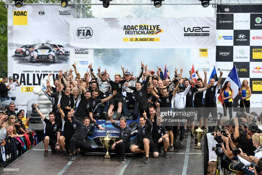 Ott Tanak of Estonia and his co- driver Martin Jarveoja of Estonia (C) celebrate with their team after they finish at the first place in front of Andreas Mikkelsen and Anders Jaeger of Norway and 3rd place Sebastien Ogier and Julien Ingrassia of France during the WRC Germany on August 20, 2017 in Neunkirchen, western Germany, near Saarbruecken. /