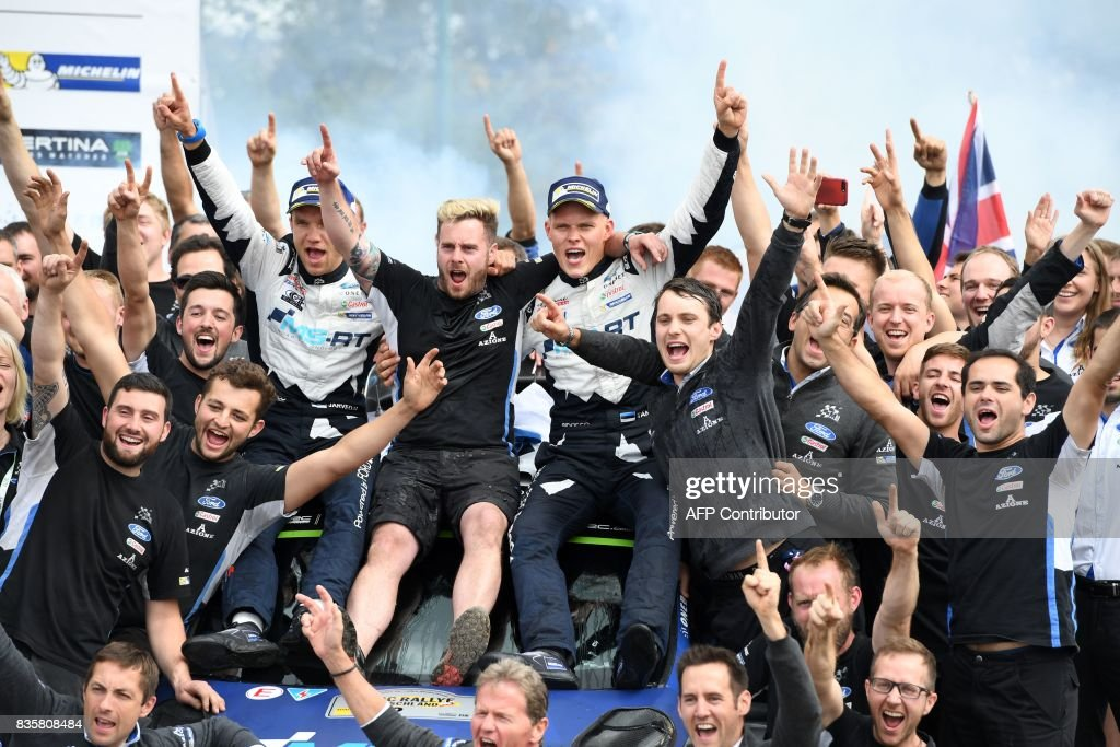 TOPSHOT - Ott Tanak of Estonia and his co- driver Martin Jarveoja of Estonia celebrate with their team after they finish at the first place in front of Andreas Mikkelsen and Anders Jaeger of Norway and 3rd place Sebastien Ogier and Julien Ingrassia of France during the WRC Germany on August 20, 2017 in Neunkirchen, western Germany, near Saarbruecken. /