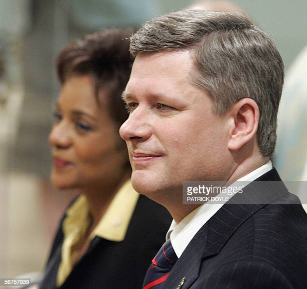 Stephen Harper , the new Prime Minister of Canada, watches his cabinet ministers being sworn in with Governor General Michaelle Jean during a...