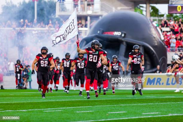 Ottawa RedBlacks defensive back Jean Philippe Bolduc runs out for player entrance carrying the #RNation flag before Canadian Football League action...