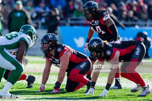 Ottawa RedBlacks defensive lineman Zack Evans and other members of the defensive line prior to the snap during Canadian Football League Eastern...