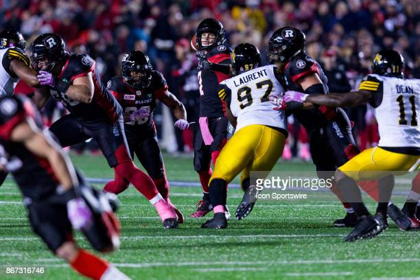 Ottawa RedBlacks quarterback Trevor Harris looks for an open receiver to pass to during Canadian Football League action between Hamilton TigerCats...