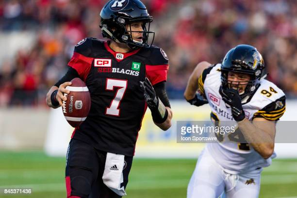 Ottawa RedBlacks quarterback Trevor Harris moves to avoid a sack as he looks for an open receiver during Canadian Football League action between...