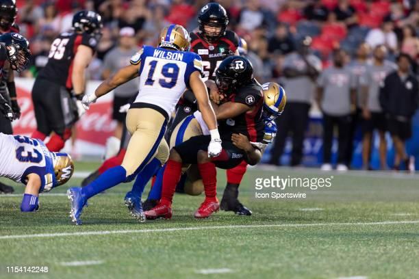 Ottawa Redblacks running back Mossis Madu Jr. Is tackled by Winnipeg Blue Bombers defensive lineman Steven Richardson during Canadian Football League...