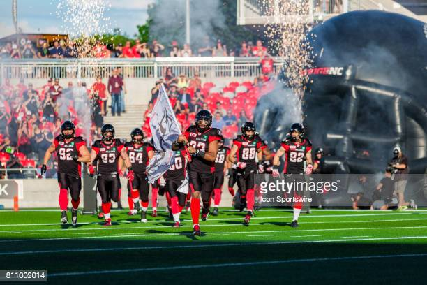 Ottawa RedBlacks running back Mossis Madu Jr runs out with the #RNation flag before Canadian Football League action between the Toronto Argonauts and...