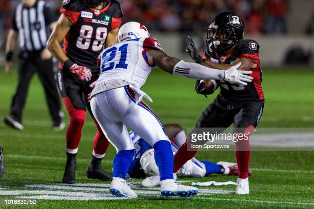 Ottawa Redblacks running back William Powell attempts to avoid a tackle from Montreal Alouettes linebacker Chris Ackie during Canadian Football...