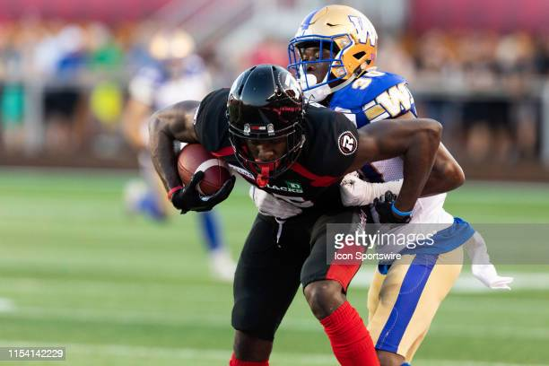Ottawa Redblacks wide receiver Dominique Rhymes attempts to break a tackle by Winnipeg Blue Bombers defensive back Winston Rose during Canadian...
