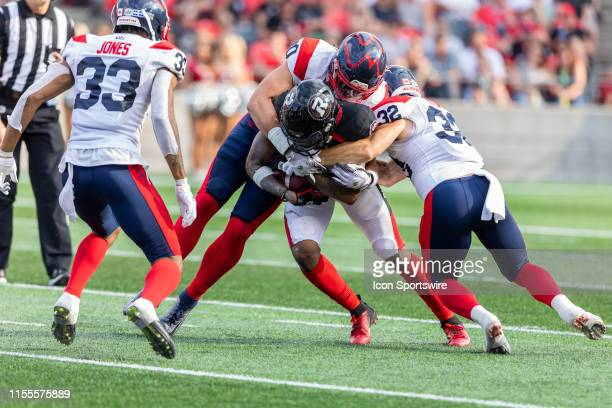 Ottawa Redblacks wide receiver R.J. Harris is brought down by Montreal Alouettes linebacker Brandon Calver and Montreal Alouettes running back Ryder...