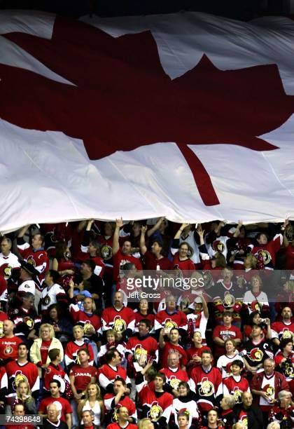 Ottawa Senator fans hold a Canadian flag during the National Anthem prior to the start of Game Four of the 2007 Stanley Cup finals between the...