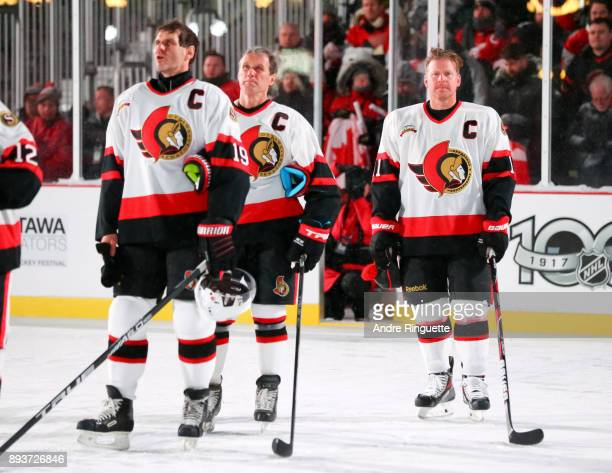 Ottawa Senators alumni Alexei Yashin Laurie Boschman and Daniel Alfredsson line up for the Canadian national anthem during the 2017 Scotiabank NHL100...