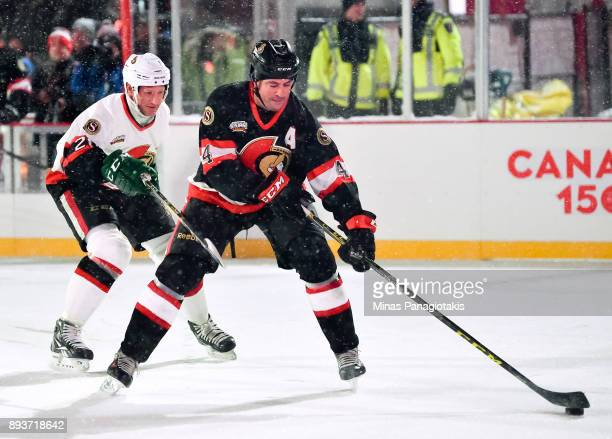Ottawa Senators alumni Chris Phillips stickhandles the puck with pressure from Magnus Arvedson during the 2017 Scotiabank NHL100 Classic Ottawa...