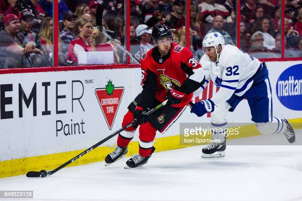 Ottawa Senators center Colin White skates the puck out from behind the net with Toronto Maple Leafs left wing Josh Leivo giving chase during third...