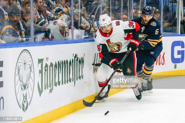 Ottawa Senators center Colin White skates to loose puck as Buffalo Sabres defenseman Marco Scandella trails the play during the Ottawa Senators and...