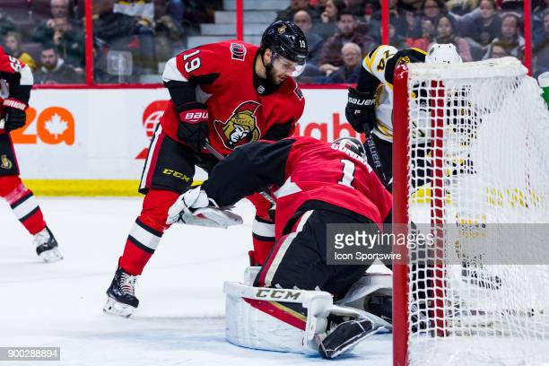 Ottawa Senators Center Derick Brassard helps Ottawa Senators Goalie Mike Condon cover the puck during first period National Hockey League action...