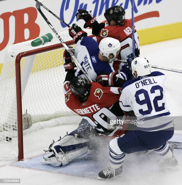 Ottawa Senators Chris Neil and Antoine Vermette crash the net as Toronto defenceman Ian White and Jeff O'Neill look on in the NHL season opener for...