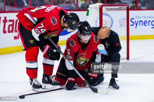 Ottawa Senators Defenceman Chris Wideman is helped off the ice by Ottawa Senators Defenceman Mark Borowiecki and Assistant athletic therapist Domenic...