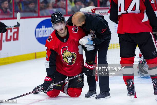 Ottawa Senators Defenceman Chris Wideman is helped up by Assistant athletic therapist Domenic Nicoletta during third period National Hockey League...