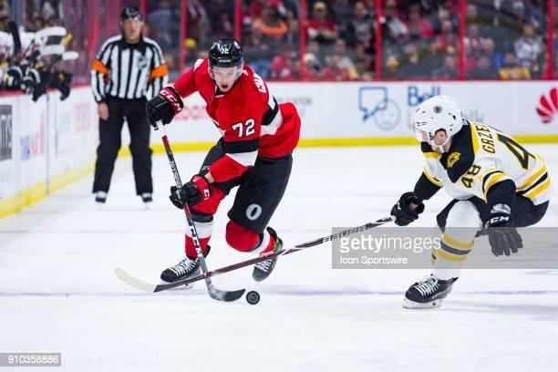 Ottawa Senators Defenceman Thomas Chabot tries to get the puck passed Boston Bruins Defenceman Matt Grzelcyk during second period National Hockey...