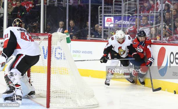 Ottawa Senators goalie Craig Anderson turns to watch Ottawa Senators right wing Bobby Ryan and Washington Capitals right wing TJ Oshie battle for the...