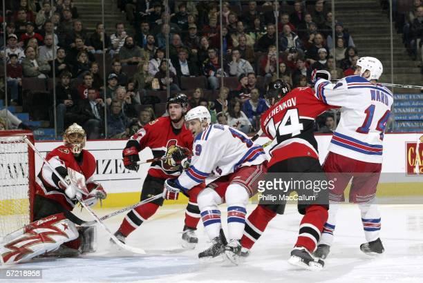 Ottawa Senators goaltender Ray Emery looks for a rebound while defensemen Andrej Meszaros and Anton Volchenkov hold up Rangers forwards Blair Betts...