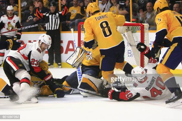 Ottawa Senators right wing Gabriel Dumont and Ottawa Senators center Nick Shore reach for the puck as Nashville Predators goalie Pekka Rinne makes a...