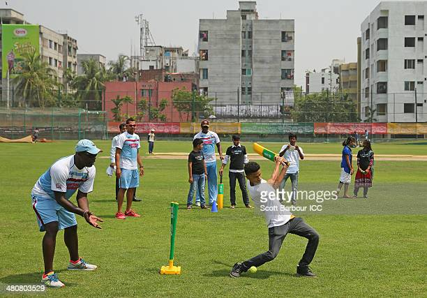 Ottis Gibson, coach of the West Indies wicketkeeps and Johnson Charles and Sunil Narine of the West Indies look on as they play a game of cricket...
