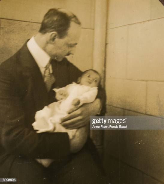 Otto Frank father of Anne Frank holds his infant daughter Margot on the balcony of his home Frankfurt am Main Germany Taken from the photo album of...
