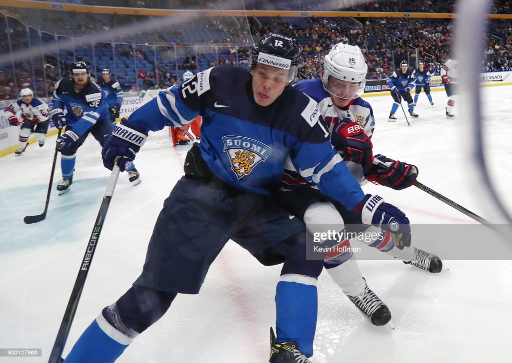 Otto Koivula #12 of Finland with the puck in the corner Kieffer Bellows #23 of United States in the third period during the IIHF World Junior Championship at KeyBank Center on December 31, 2017 in Buffalo, New York. The United States beat Finland 5-4.