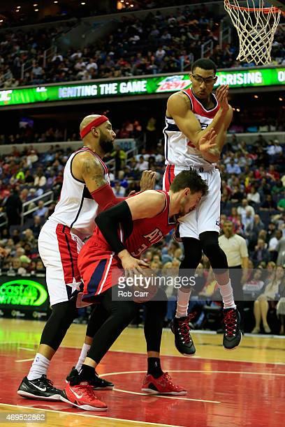Otto Porter Jr #22 of the Washington Wizards fouls Mike Muscala of the Atlanta Hawks as Drew Gooden of the Washington Wizards looks on during the...