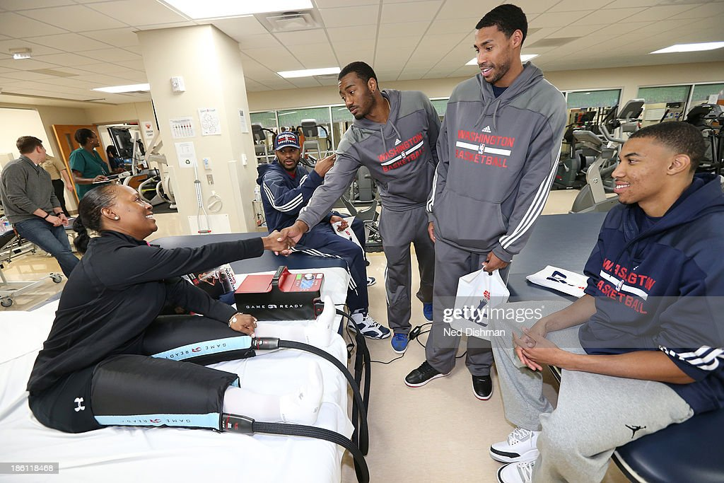 Otto Porter Jr #22, John Wall #2 and Trevor Booker #35 of the Washington Wizards greet a patient during a visit to Walter Reed Medical Center on October 25, 2013 in Washington, DC.