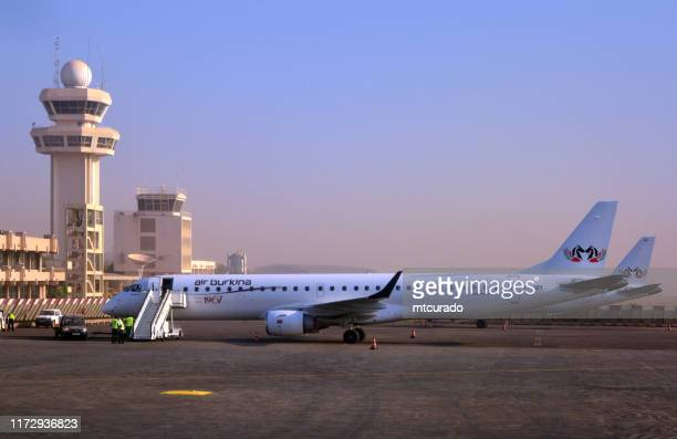 ouagadougou airport - control tower and air burkina embraer 195, ouagadougou, burkina faso - burkina faso stock pictures, royalty-free photos & images