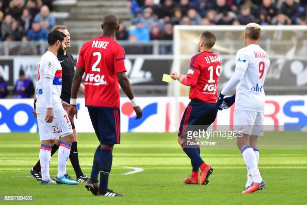 Oualid El Hajjam of Amiens returns the yellow card to referee Olivier Thual after he had dropped it during the Ligue 1 match between Amiens SC and...