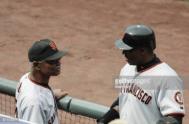 Oufielder Barry Bonds of the San Francisco Giants talks to his manager Felipe Alou during the game against the Colorado Rockies at Coors Field on...