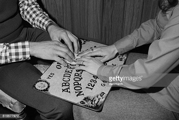 Ouija Board Man and woman with hands on board seek message of spiritualistic or telepathic origin