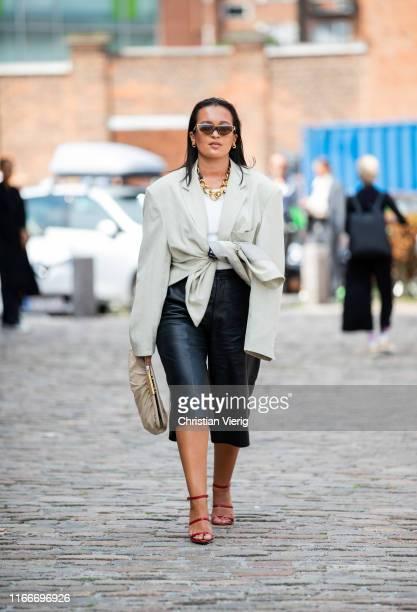 Oumayma Elboumeshouli is seen wearing black cropped leather pants, belted blazer, clutch outside Rodebjer during Copenhagen Fashion Week...