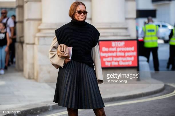 Oumayma Elboumeshouli wearing black pleater skirt slip over outside Victoria Beckham during London Fashion Week September 2019 on September 15 2019...