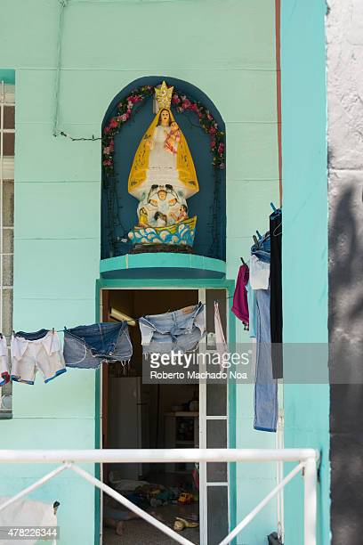 Our Lady of El Cobre, patroness of Cuba, at the entrance of a house in Havana, everyday scene with clothes hanging on clothesline in front of.