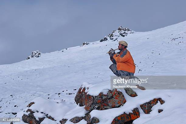 Our Porter at Machloo La in Northeren Pakistan , Sitting on top during a snow falling day and blowing flute. Machloo la is very famous for the view...