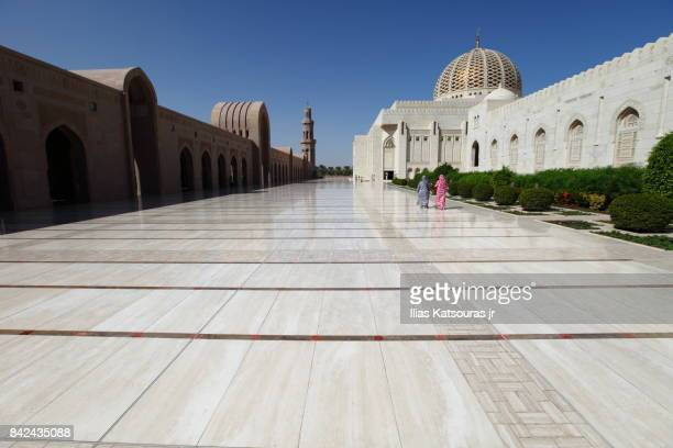 ourists covered in colorful garments walk along the exterior courtyard of the Sultan Qaboos Grand Mosque, in Musqat, Oman