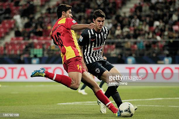 Ousama Darragi of Esperance Sportive de Tunis is challenged by Hiram Mier of Monterrey during the FIFA Club World Cup 5th Place match between Club de...