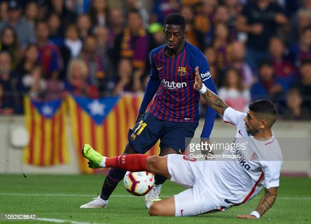 Ousmane Dembele of Barcelona competes for the ball with Ever Banega of Sevilla during the La Liga match between FC Barcelona and Sevilla FC at Camp...