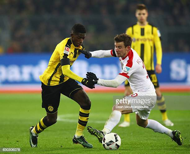 Ousmane Dembele of Borussia Dortmund takes on Daniel Baier of FC Augsburg during the Bundesliga match between Borussia Dortmund and FC Augsburg at...