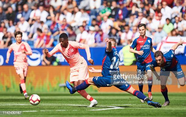 Ousmane Dembele of FC Barcelona duels for the ball with Jorge Pulido of SD Huesca during the La Liga match between SD Huesca and FC Barcelona at...