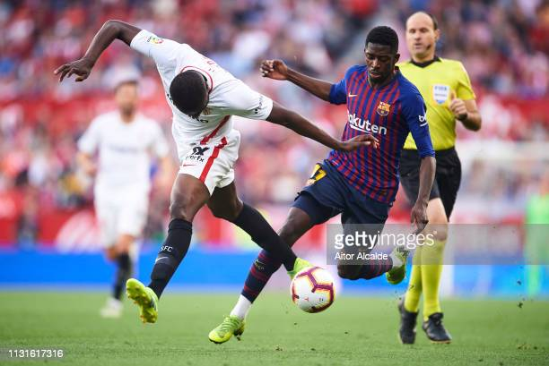 Ousmane Dembele of FC Barcelona duels for the ball with Luis Muriel of Sevilla FC during the La Liga match between Sevilla FC and FC Barcelona at...