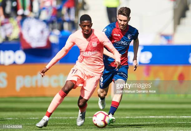 Ousmane Dembele of FC Barcelona duels for the ball with Moises Gomez of SD Huesca during the La Liga match between SD Huesca and FC Barcelona at...