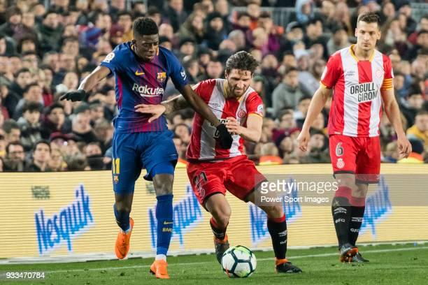 Ousmane Dembele of FC Barcelona fights for the ball with Carles Planas Antolinez of Girona FC during the La Liga 201718 match between FC Barcelona...