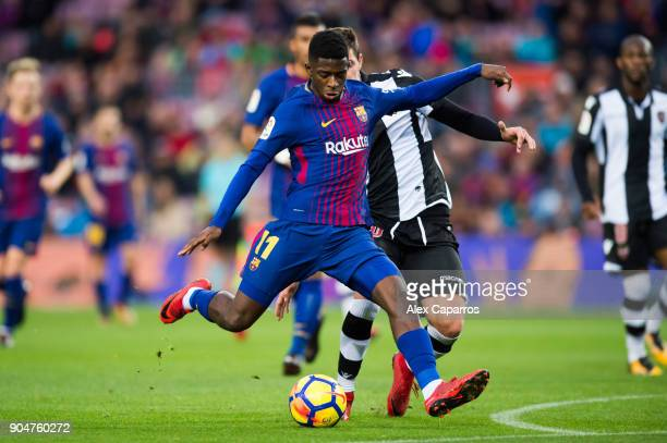 Ousmane Dembele of FC Barcelona kicks the ball under pressure from Sasa Lukic of Levante UD during the La Liga match between Barcelona and Levante at...