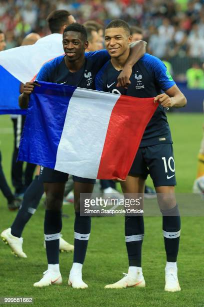 Ousmane Dembele of France and Kylian Mbappe of France celebrate victory with a tricolore flag after the 2018 FIFA World Cup Russia Final between...